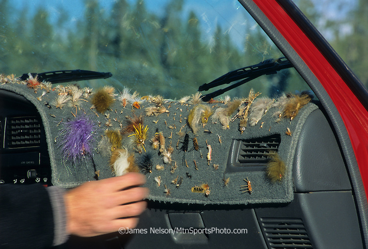 A fishing guide selects a fly from the dashboard of his fishing vehicle along the Henry's Fork (a.k.a., North Fork) of the Snake River in Idaho.