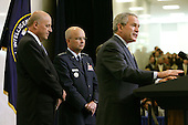 Langley, VA - May 31, 2006 -- United States President George W. Bush, right, speaks during a ceremonial swearing in for new Central Intelligence Agency Director General Michael Hayden, Center, as National Intelligence Director John Negroponte looks on, at CIA headquarters in Langley, Virginia Wednesday 31 May 2006. Hayden, the former head of the super-secret National Security Agency (NSA), was officially sworn-in yesterday in a closed ceremony.<br /> Credit: Matthew Cavanaugh-Pool via CNP