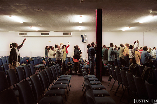 Ex-addicts and prostitutes pray at the Amsterdam church of Victory Outreach...The controversial church started in Los Angeles in 1967, is spreading to Europe via the Netherlands. It builds its membership among junkies, prostitutes and criminals. ..Photo taken in the Netherlands in 2002. The picture is part of a photo and text documentary by Justin Jin. For more information, email justin@justinjin.com