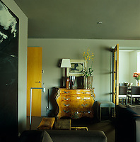 An antique chest of drawers contrasts with the contemporary furniture with which the living room has been decorated