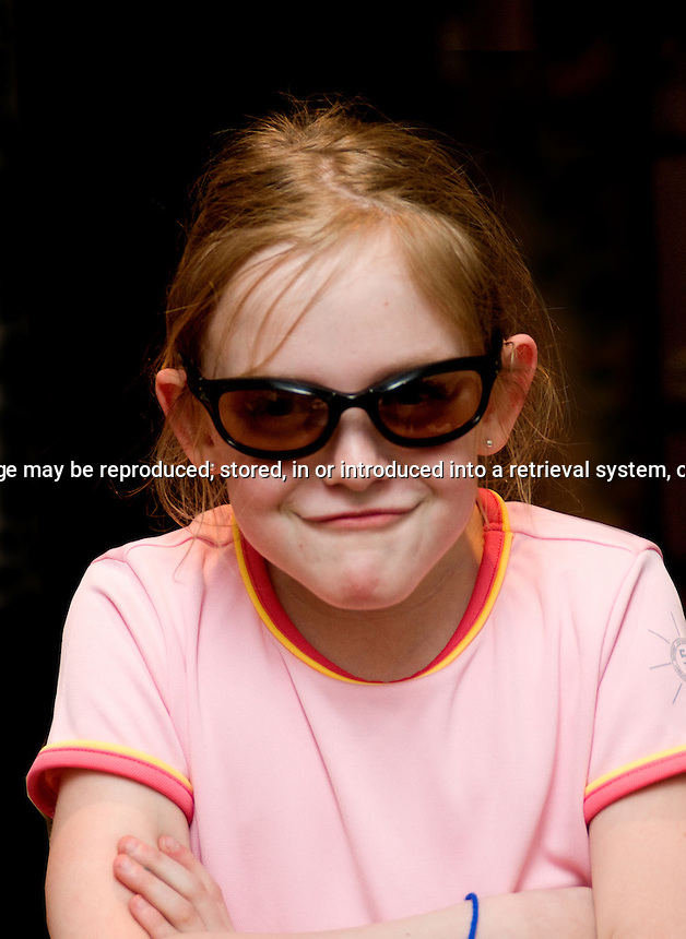 Young girl with sunglasses making a funny face