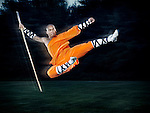 Shaolin warrior monk in mid-air flying kick jump with a staff outdoors