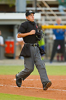 Home plate umpire Takahito Matsuda hustles down the first base line during the Appalachian League game between the Danville Braves and the Burlington Royalsat Burlington Athletic Park on August 16, 2013 in Burlington, North Carolina.  The Royals defeated the Braves 1-0.  (Brian Westerholt/Four Seam Images)