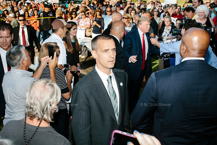 Security watches the crowd as real estate mogul and Republican presidential candidate Donald Trump arrives at a rally at the Weirs Beach Community Center in Laconia, New Hampshire.