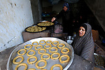 A Palestinian family make traditional date-filled cookies in preparation for the Eid al-Fitr holiday at their home in Rafah, in the southern Gaza Strip, on June 23, 2017. Muslims around the world are preparing to celebrate the Eid al-Fitr holiday, which marks the end of the fasting month of Ramadan. Photo by Abed Rahim Khatib