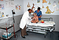 Pediatric doctor and nurse attending to a child in an accident and emergency department of a hospital. The child .was brought in after falling over and cutting open the back of his head. The doctor is using a stethoscope to listen to the childs heart and lungs whilst the nurse is assessing the wound...© SHOUT. THIS PICTURE MUST ONLY BE USED TO ILLUSTRATE THE EMERGENCY SERVICES IN A POSITIVE MANNER. CONTACT JOHN CALLAN. Exact date unknown.john@shoutpictures.com.www.shoutpictures.com..