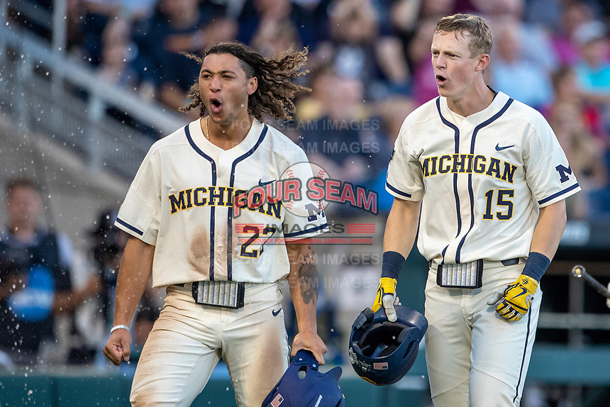 Michigan Wolverines outfielder Jordan Brewer (22) celebrates with teammate Jimmy Kerr (15) after scoring against the Vanderbilt Commodores during Game 1 of the NCAA College World Series Finals on June 24, 2019 at TD Ameritrade Park in Omaha, Nebraska. Michigan defeated Vanderbilt 7-4. (Andrew Woolley/Four Seam Images)