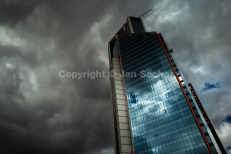 A Colombian window cleaner works outside the Atrio North Tower building before the rainstorm in Bogotá, Colombia, 24 October 2019.