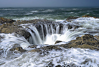 High tide seawater pours into a coastline rock hole called Thor's Well, Cape Perpetua, Oregon