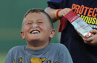 A young fan tries to slide a piece of candy from his forehead into his mouth without using his hands during a between-innings game on August 4, 2012, at TicketReturn.Com Field in Myrtle Beach, South Carolina. Myrtle Beach won, 4-3. (Tom Priddy/Four Seam Images)