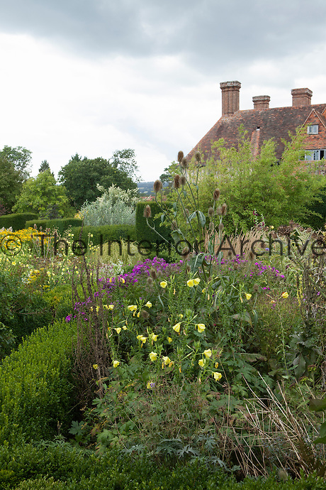 Mature summer border at Great Dixter with house beyond