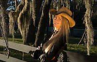 attractive 50 year old blonde woman cowgirl with a hat outdoors leaning against fence with spanish moss