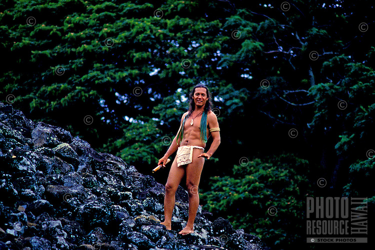 An attractive local man wearing a loin cloth stands beside Ulupo Heiau near Kailua on the windward side of Oahu.
