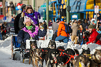 Jodi Bailey and her Iditarider are all smiles as they run down 4th avenue after leaving  the Ceremonial Start line of the 2016 Iditarod in Anchorage, Alaska.  March 05, 2016