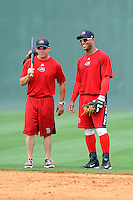 Second baseman Yoan Moncada (24) of the Greenville Drive, right. talks with manager Darren Fenster before a game against the Lexington Legends on Monday, May 18, 2015, at Fluor Field at the West End in Greenville, South Carolina. Moncada, a 19-year-old prospect from Cuba, made his professional debut tonight in the Red Sox organization. (Tom Priddy/Four Seam Images)
