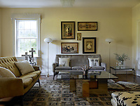 The living room's neutral grey and pale yellow colour scheme complements a set of Victorian illustrations and a collection of crosses