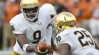 Irish quarterback Malik Zaire (9) hands off to running back Tarean Folston (25) in the second quarter.