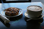 hot coffee drink with pastry on table in urban cafe.