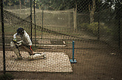 A young batsman defends the ball during net practice at a club in Maidan in Kolkata, West Bengal, India.