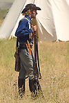 A participant in the annual Custer Battle at the Little Bighorn reenactment appears as a pioneer of the old west with a tee pee in the background. Hardin, Montana. Model Release
