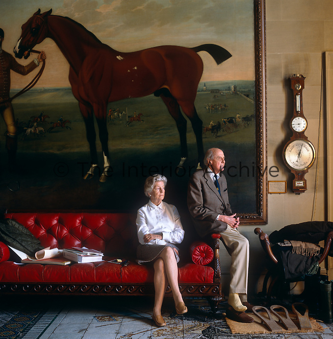 Portrait of the late Duke of Devonshire and the late Dowager Duchess seated in front of a painting by George Stubbs in the West Hall at Chatsworth