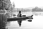 A woman looks out on the calm waters of Tully lake from her kayak Woman paddling a kayak on a very calm lake