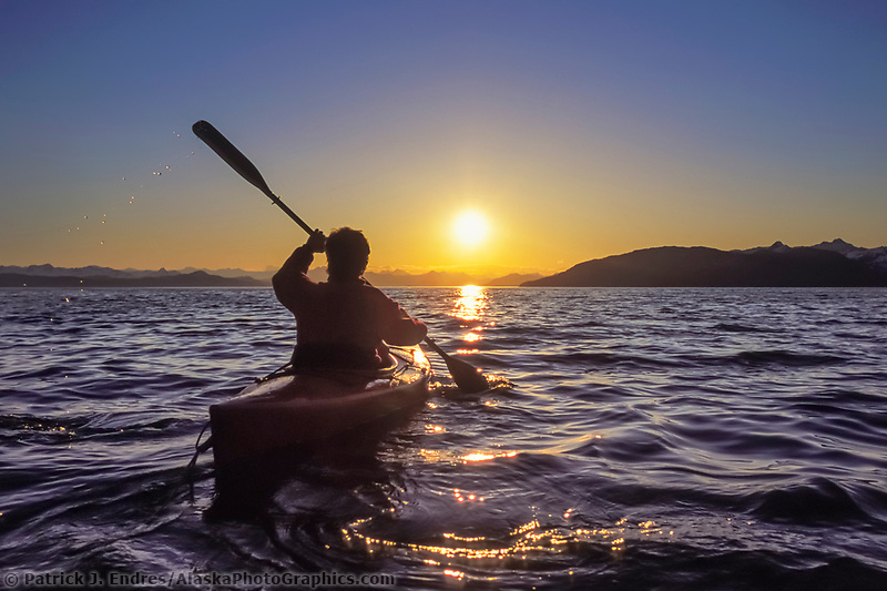 Sea kayaker paddles in the sunset light off the shore of Knight Island, Prince William Sound, Alaska.