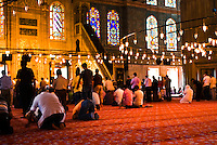 Men praying at the blue Mosque (Sultan Ahmet mosque), Istanbul (Turkey).