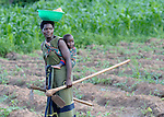Baby on board, a woman walks home from working in her farm field in Zombwe, in northern Malawi.