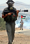 An Israeli Soldier getting ready to fire a tear gas during clashes with Palestinian demonstrators following a weekly protest against the Jewish settlement of Kdumim, near Nablus,in the northern West Bank village of Kufr Qaddum,  June 22, 2012. According to medical sources, eight Palestinians were injured during the clashes. Photo by Nedal Eshtayah