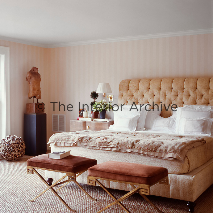 A comfortable double bed with a high buttoned headboard dominates the master bedroom which has been decorated in a natural colour palette