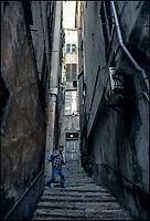 Genova, una persona in uno stretto vicolo tra vecchie case --- Genoa, a person in a narrow alley between shabby houses