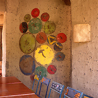 A simple dining room with a patterned paint effect on the mud walls. Several blue metal chairs are placed at wooden tables.