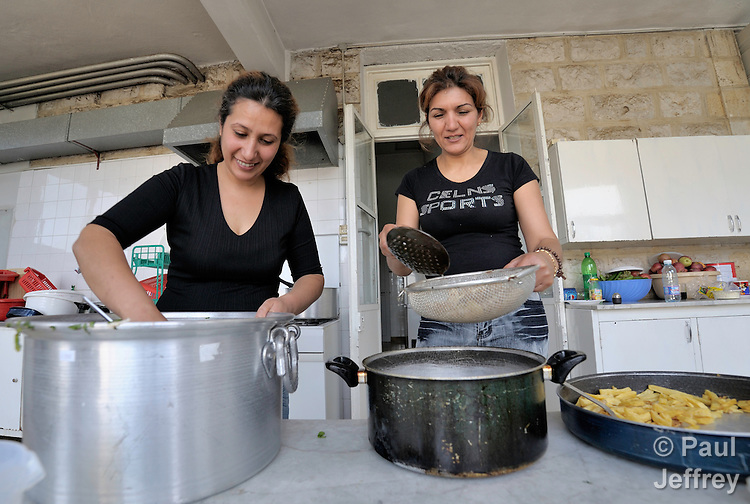 Two Iraqi women--Souad Wahid Aatwaan (left) and Shatha Hakmat Tobia--prepare food for themselves and others in a shelter outside Beirut for Iraqi refugees and other residents of Lebanon who have suffered from domestic violence. The shelter, a program of the Caritas Lebanon Migrant Center, which is funded by Catholic Relief Services, the relief and development agency of the U.S. Catholic community, is located in an unnamed community on the outskirts of Beirut.