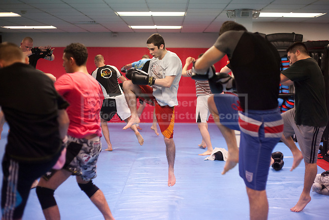 A student takes to the air as he practices a knee strike during a session concentrating on striking an opponent.  Of those going to class the majority attend with a view to keeping fit, rather than competing or as a way to defend themselves.