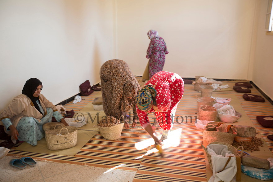 """Morocco - Tidzi - Women of the Ajddigue cooperative cleaning up the room where they crush the nuts after a day at work. <br /> The cooperative produces around 20 tons of argan oil per year, with a turnover of around 100,000 euros. Despite having contributed to the empowerment of thousands of rural women, the argan oil cooperatives are now threatened by the industrial plants set up in Casablanca and Agadir, which are able to extract much more oil in less time. """"Our cooperatives might disappear in 5 or 10 years"""" confesses Zahra Knabo, the director at Ajddigue."""