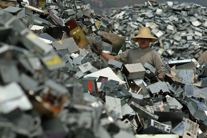 A junk yard worker sorts e-waste worker makes plastic flowers out of recycled plastics in Nanyang, China.