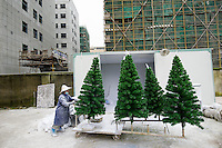 November 28, 2015, Yiwu China - A worker in surgical mask pushes a trolley of Christmas tree which will soon be sprayed with artificial snow. The mask is to prevent the worker breathing in the artificial snow. Sinte An factory produces a variety of artificial trees for global export throughout the year.Photo by Dave Tacon / Sinopix