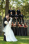 First look with groom seeing his bride for the first time, with the bridal party against a stone wall, on the beautiful grounds of Tarrytown House in the Hudson Valley.