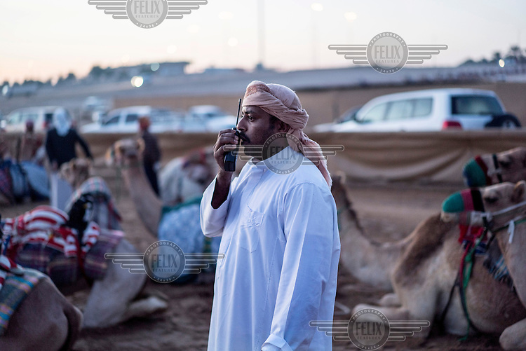 A racing camel owner tests the radio that will be placed on the robot jockey so that during the race the owner can shout commands to the camel from his SUV as he follows the race.