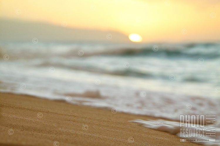 gentle waves wash over the sandy beach at sunset