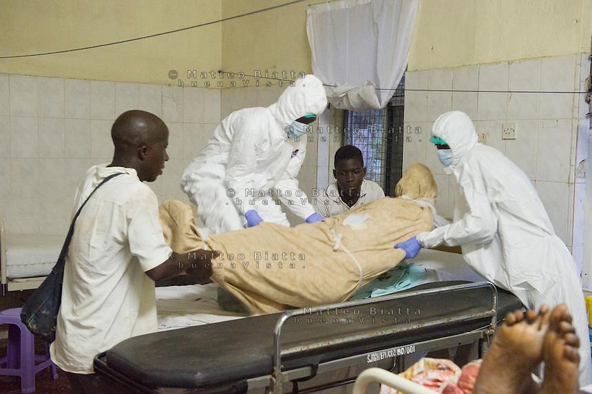 Fatebenefratelli Ospedale Saint John of God di Lunsar nella foto gli addetti al trasporto delle salme svolgono il loro lavoro indossando il PPE (Personal Protective Equipment) per eliminare ogni probabilit&agrave; di contrarre qualunque malattia infettiva. Questa regola &egrave; presente in ospedale da quando &egrave; scoppiata l'epidemia di Ebola. Purtroppo i parenti dei defunti non rispettano questa regola, rendendo inutile ogni precauzione sanit&agrave; Lunsar 24/03/2016 foto Matteo Biatta<br /> <br /> Fatebenefratelli Hospital Saint John of God in Lunsar in the picture men carrying the bodies wear PPE (Personal Protective Equipment) for excluding any chances of contract any contagious disease. This rule is present in the hospital since Ebola outbreak begin. Unfortunately, the relatives of the deceased do not respect this rule, rendering useless any precaution health Lunsar 24/03/2016 photo by Matteo Biatta