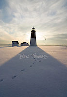 Footprints in the snow meander passed the Point Judith Lighthouse