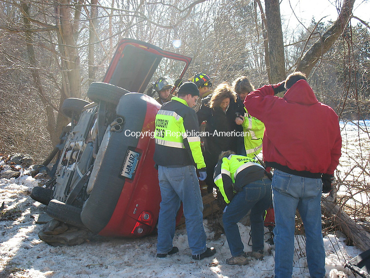 WOODBURY, CT - 123008RH01 - Emergency responders help Diane M. Miller of Middlebury from her car after she lost control and crashed into a stone wall on Minortown Road Tuesday. Miller, 51, was driving a 2008 red Volkswagen Rabbit north on Minortown Road at about noon when she hit a patch of sand around a bend, oversteered and struck a wall, causing the car to flip on its side, police said. Miller was not injured, police said.