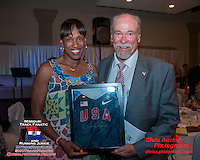 Herculaneum coach Jim Kasten poses with Jackie Joyner-Kersee after winning the auction for a Joyner-Kersee signed USA Track and Field jersey at the 2013 Brittany Borman Olympic Celebration in Festus, MO. Friday, September 13.