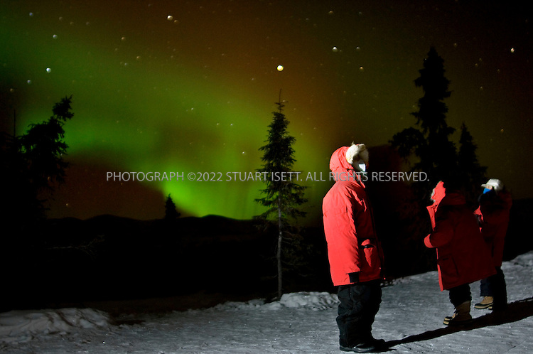2/12/2007--Fairbanks, Alaska, USA..A group of Japanese tourists enjoy the Northern Lights from a hill near the Chena Hot Springs Resort about 60 miles east of Fairbanks, Alaska. ..The Fairbanks/Chena area is the epicenter of Japanese winter tourism in the state, because it affords the best viewing areas for the Northern Lights. At least 10 chartered 350-passenger Japanese Air Lines 747?s are due to arrive at Fairbanks International Airport this winter, carrying groups from Tokyo, Osaka and Nagoya. Another 3,500 or so Japanese tourists are forecast to arrive on weekly commercial flights...Photograph ©2007 Stuart Isett.All rights reserved..Photograph ©2007 Stuart Isett.All rights reserved