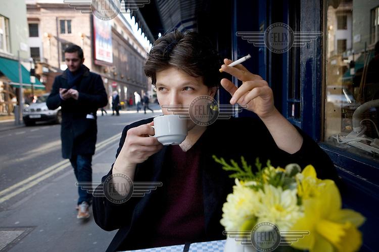 Oleg Mitrofanov drinks tea and smokes a cigarette outside of a cafe in Soho, London.