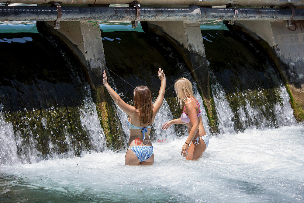 Two attractive, sexy young women enjoy the spring falls at the Barton Springs Spillway in Zilker Park, Austin, Texas.