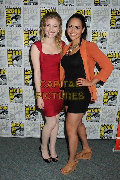 Skyler Samuels & Alyssa Diaz.Comic-Con International 2011 - Day 2 held at The San Diego Convention Center, San Diego, California, USA..July 22nd, 2011.full length red dress hand on hip braid plait hair playsuit orange jacket.CAP/ADM/BP.©Byron Purvis/AdMedia/Capital Pictures.