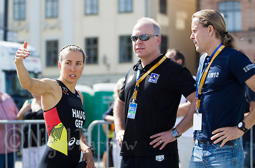 24 AUG 2013 - STOCKHOLM, SWE - Anne Haug (GER) (left) of Germany discusses the swim course with coaches before the start of the elite women's ITU 2013 World Triathlon Series round in Gamla Stan, Stockholm, Sweden (PHOTO COPYRIGHT © 2013 NIGEL FARROW, ALL RIGHTS RESERVED)